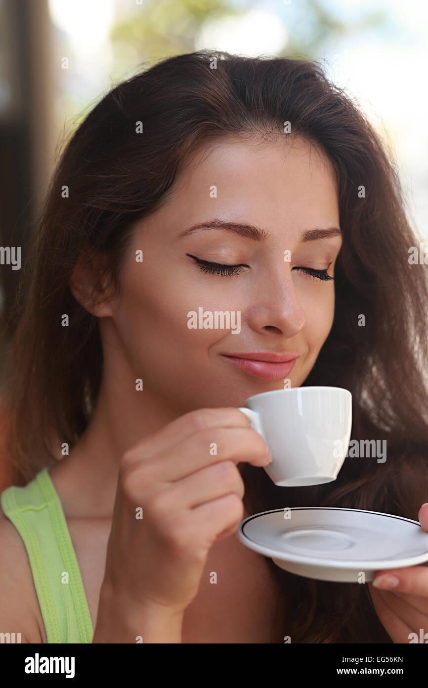 Bella donna di bere il caffè con godendo il viso e gli occhi chiusi. Closeup ritratto Immagini Stock