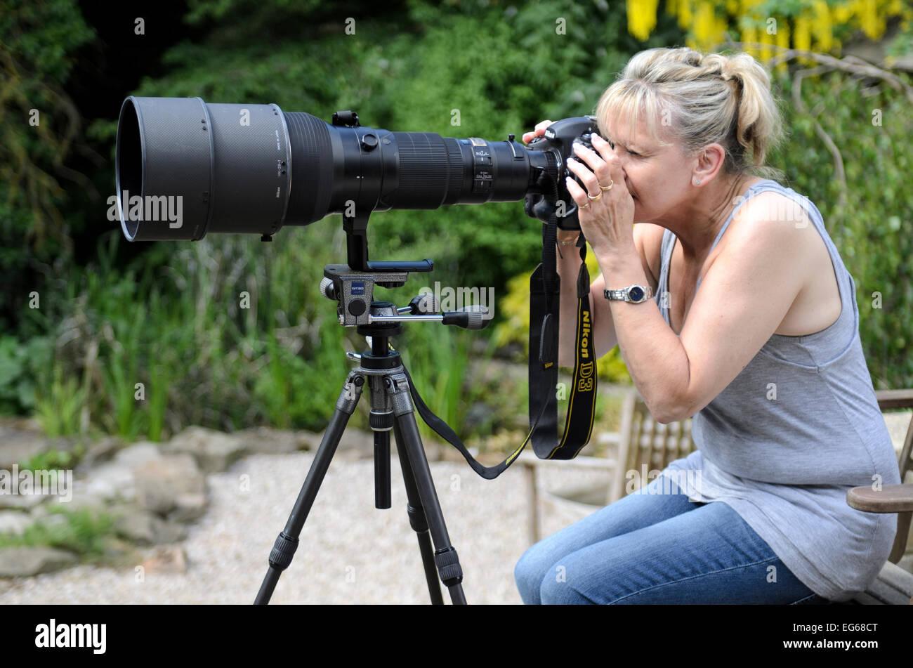 Donna che utilizza un 600 mm teleobiettivo su una Nikon D3 release disponibile Immagini Stock