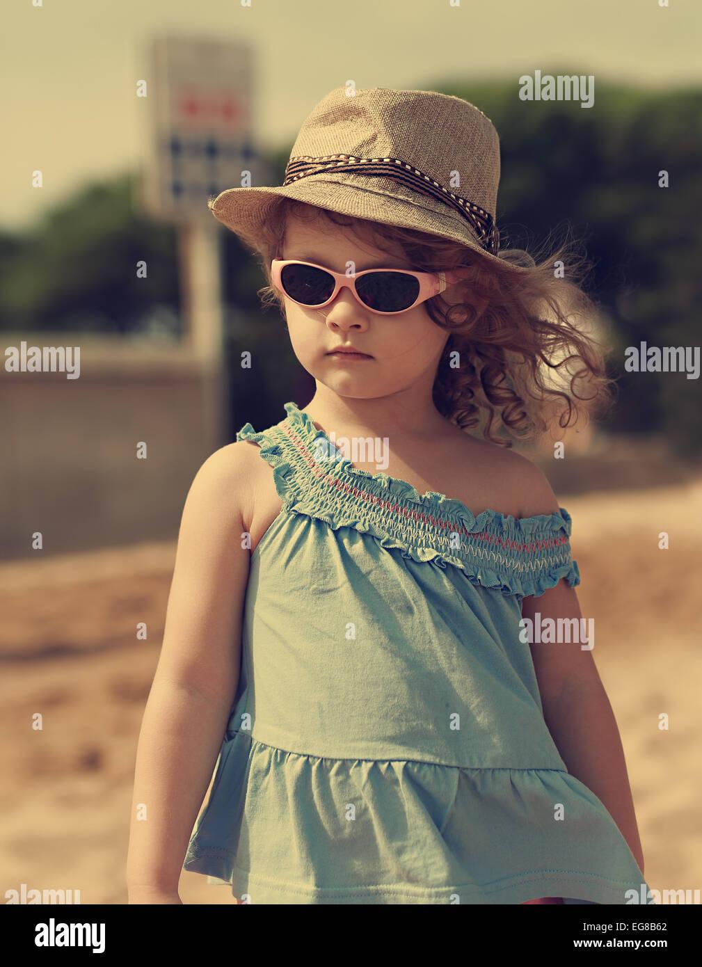 9e131a0fb39248 Bellissimi e moderni kid ragazza nel cappello e occhiali da sole guardando  all'aperto