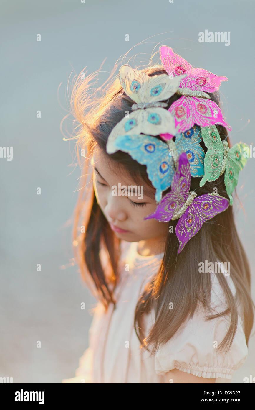 La ragazza (8-9) con farfalle sui capelli Immagini Stock