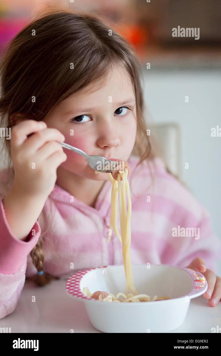Bambina (4-5) mangiare spaghetti per il pranzo Immagini Stock