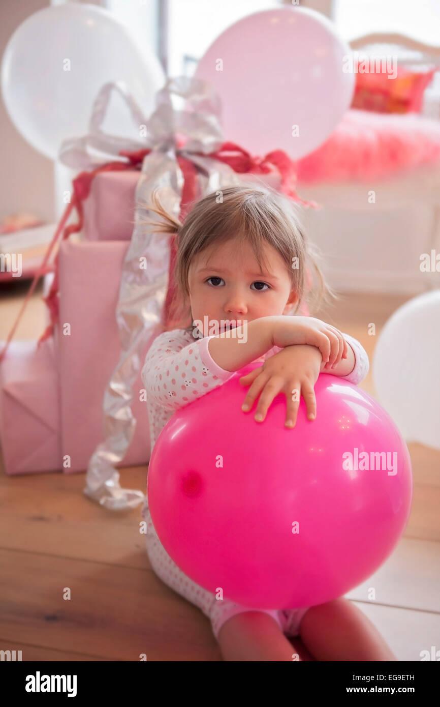 La ragazza (2-3) seduto sul pavimento con palloncino rosa Immagini Stock