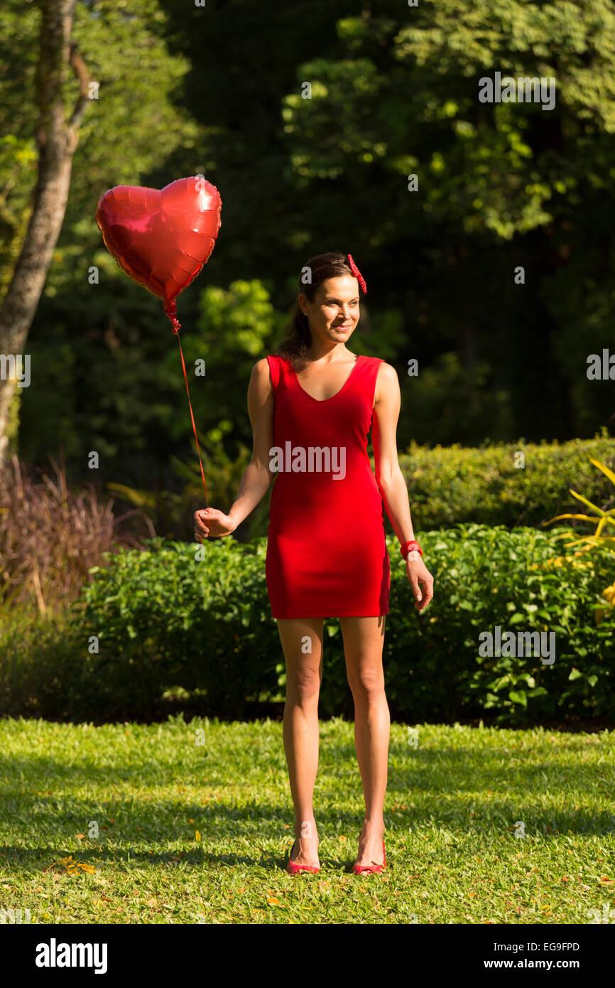 Donna con cuore rosso forma palloncino in piedi in posizione di parcheggio Immagini Stock