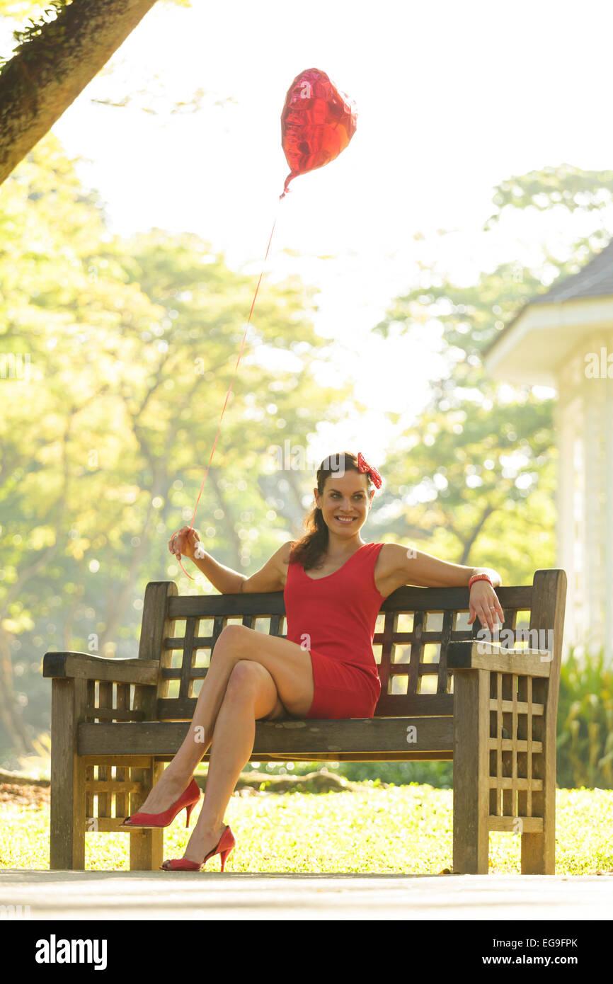 Donna con cuore rosso forma palloncino seduta su una panchina nel parco Immagini Stock