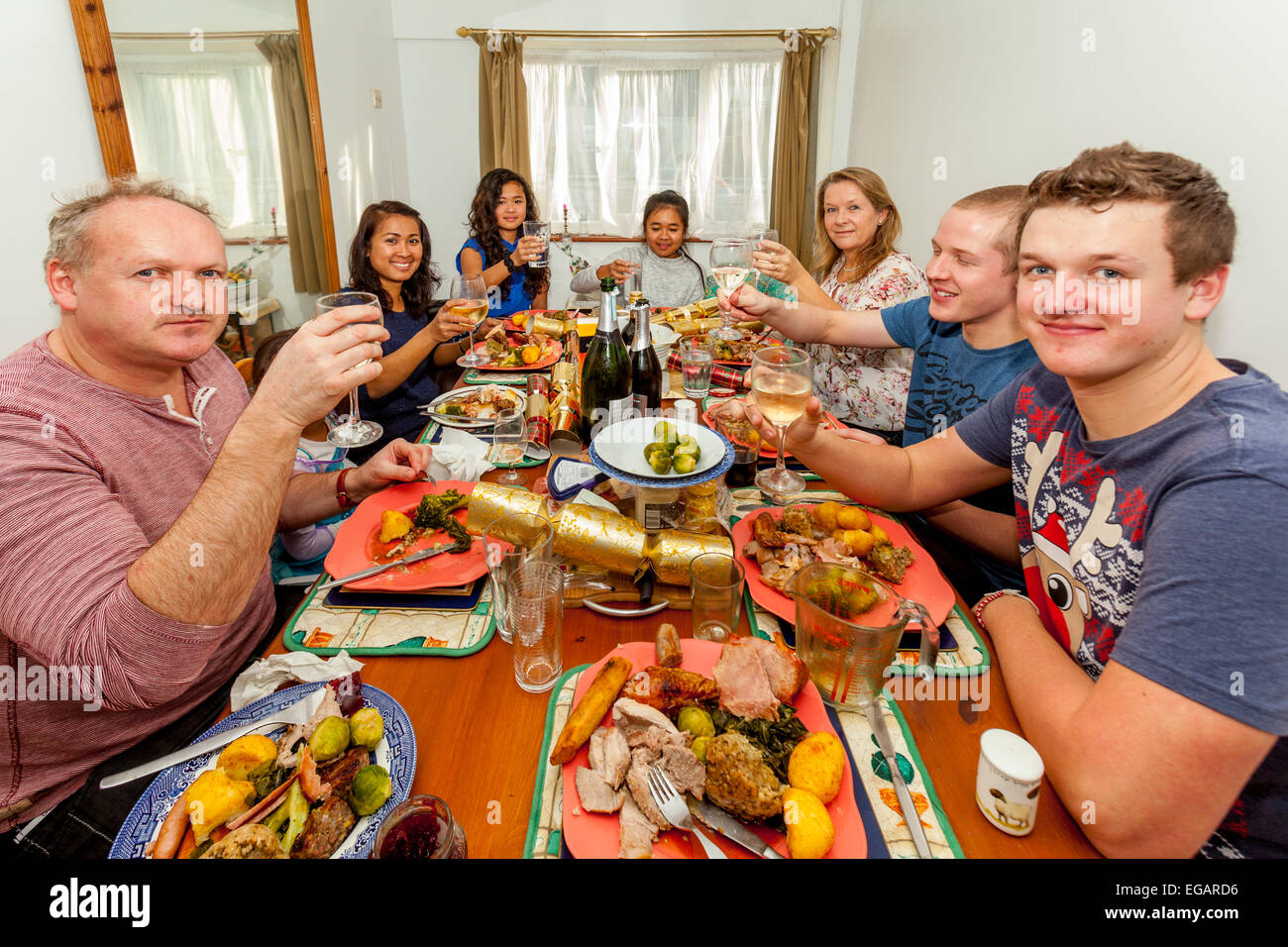 Una razza mista famiglia godendo il pranzo di Natale, Sussex, Inghilterra Immagini Stock