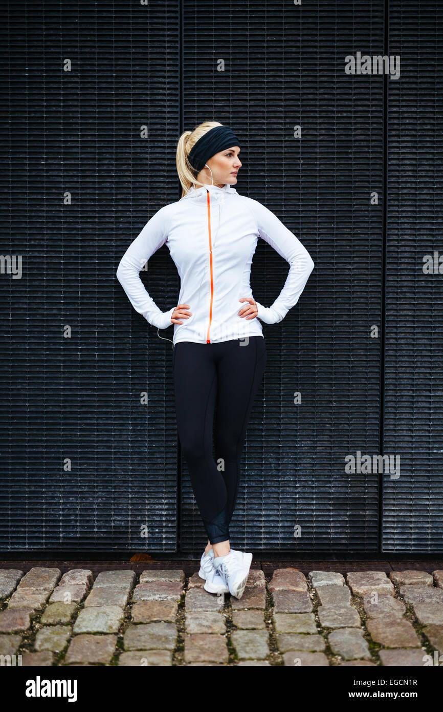 Per tutta la lunghezza di tiro sportivo da donna giovane rilassante dopo esecuzione di esercizio fisico. Atleta Immagini Stock