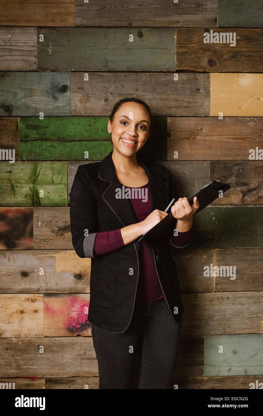 Ritratto di giovane attraente executive femmina con un blocco appunti in piedi contro una parete in legno in ufficio. Immagini Stock