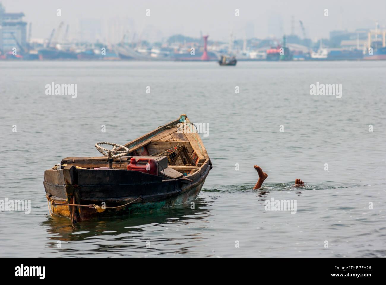 Uomo locale si tuffa per cercare ancora abbandonati elementi utili sul fondale basso di Giacarta costa. Immagini Stock