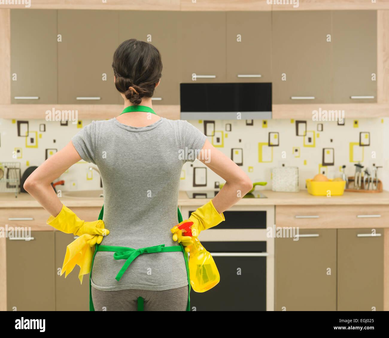 Vista posteriore del giovane massaia ottenere pronto per la pulizia della cucina Immagini Stock