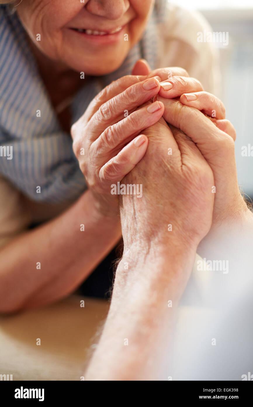 Le mani di affettuosa seniors Foto Stock