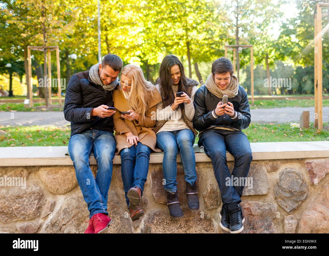Sorridendo gli amici con gli smartphone nel parco della città Immagini Stock