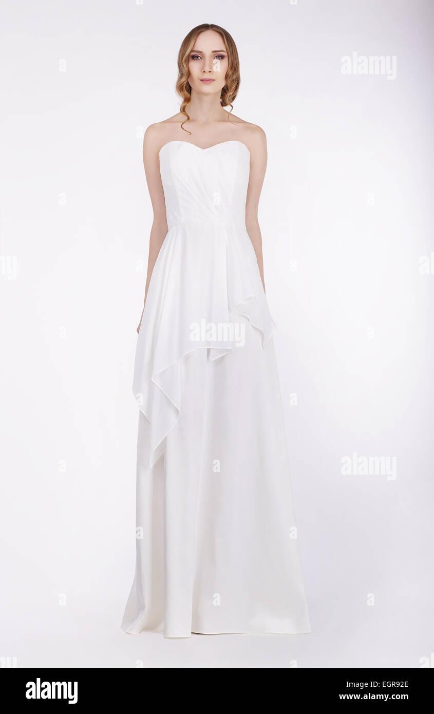 Modello di moda in piedi in lungo abito bianco Immagini Stock