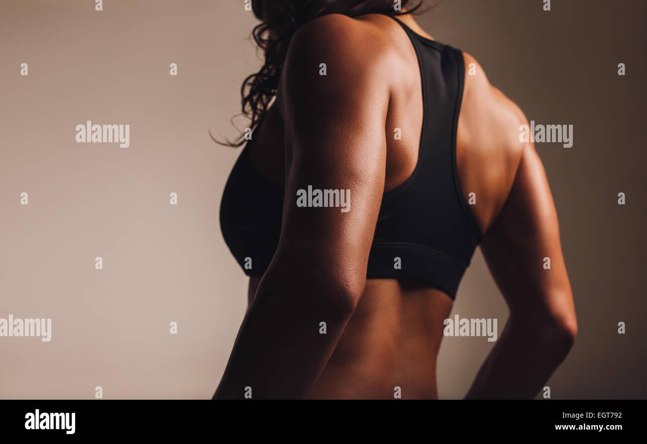 Retro di un montare e muscolare atleta donna nel reggiseno per lo sport. Vista posteriore del fitness femmina con Immagini Stock