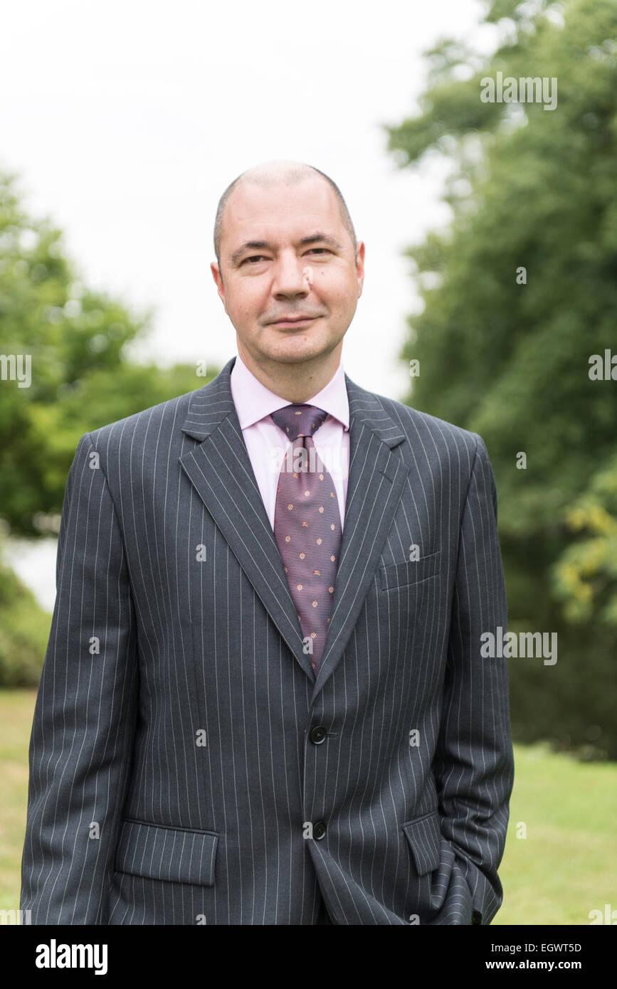 Un imprenditore professionale / hotel manager sta nei giardini di una casa di campagna inglese che indossa una tuta Immagini Stock