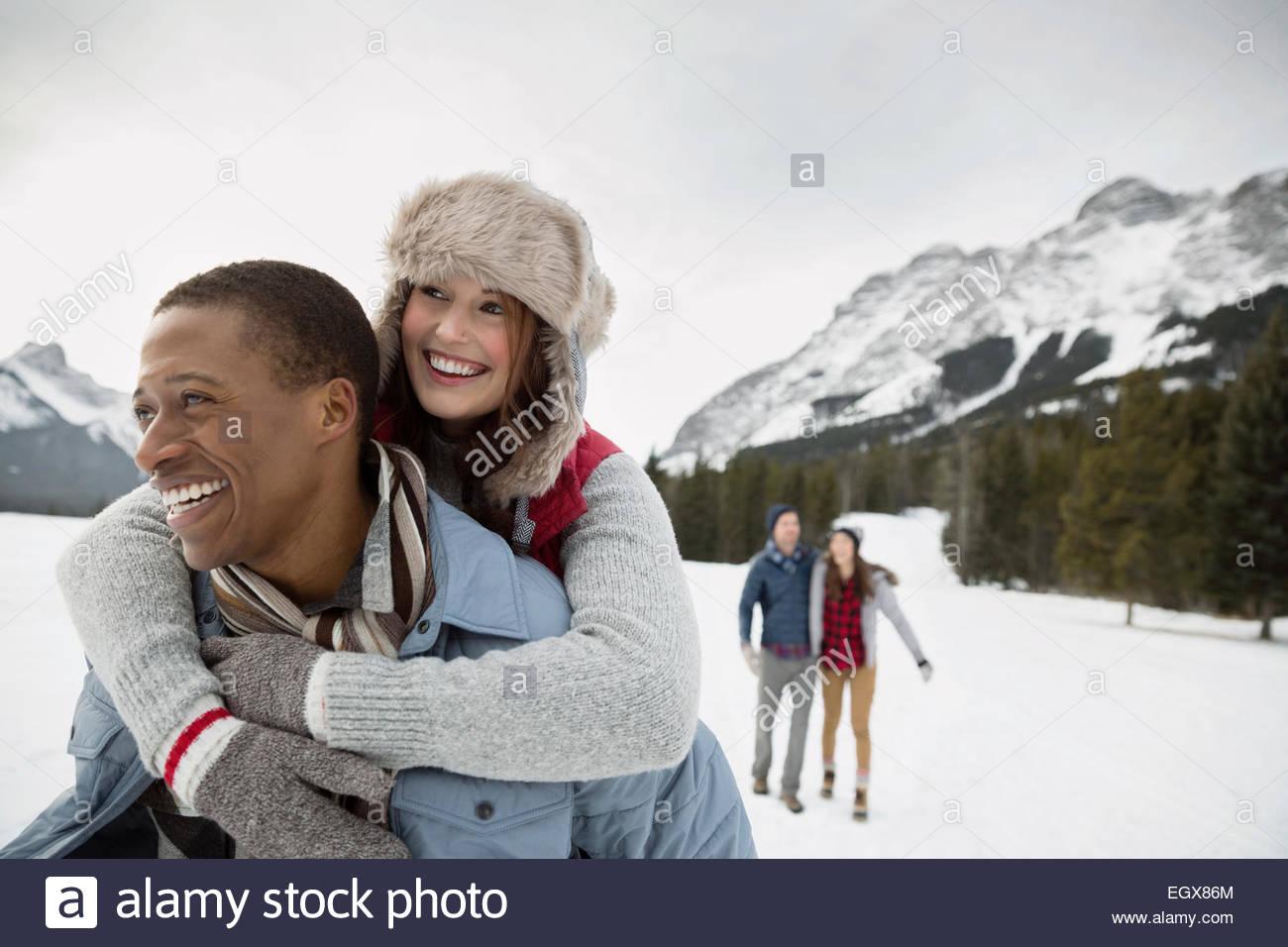 Ritratto di giovane piggybacking in campo nevoso Immagini Stock