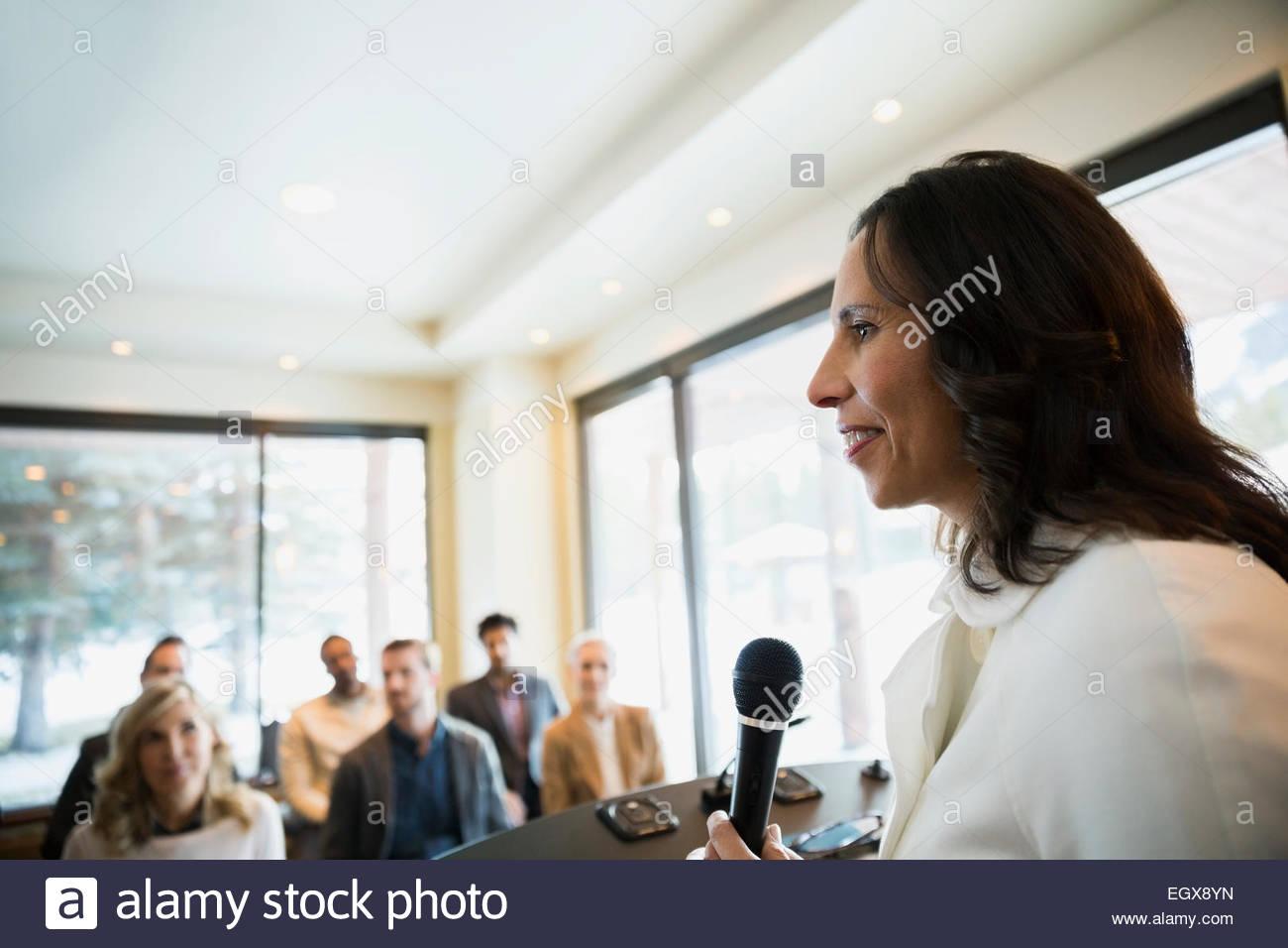 Imprenditrice con microfono principale conferenza Immagini Stock