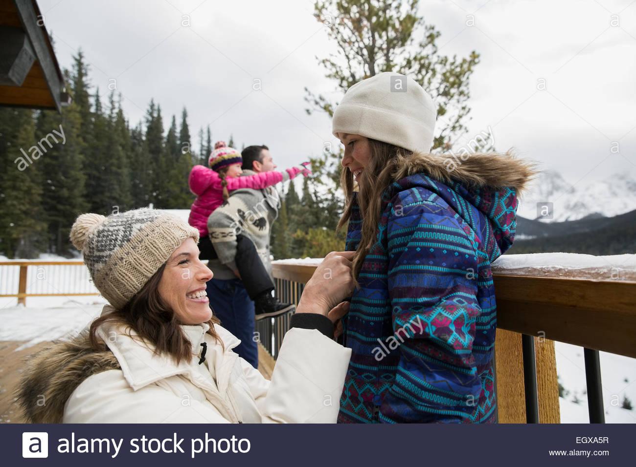 Madre aiutare mia figlia con la casacca sul ponte di neve Immagini Stock