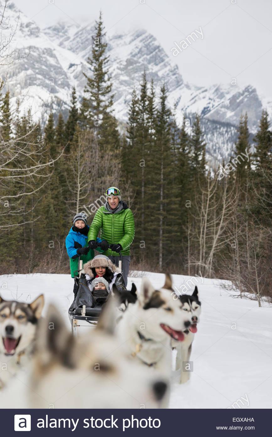 Famiglia di seguito dogsledding Montagna innevata Immagini Stock