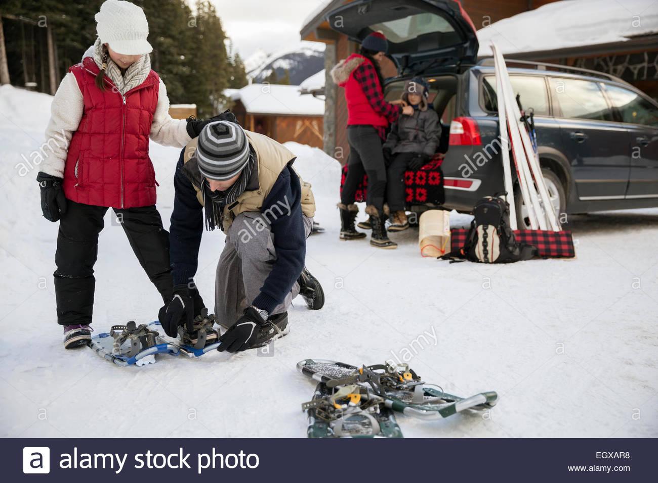 Padre di racchette da neve di fissaggio sulla nostra figlia nel vialetto innevato Foto Stock