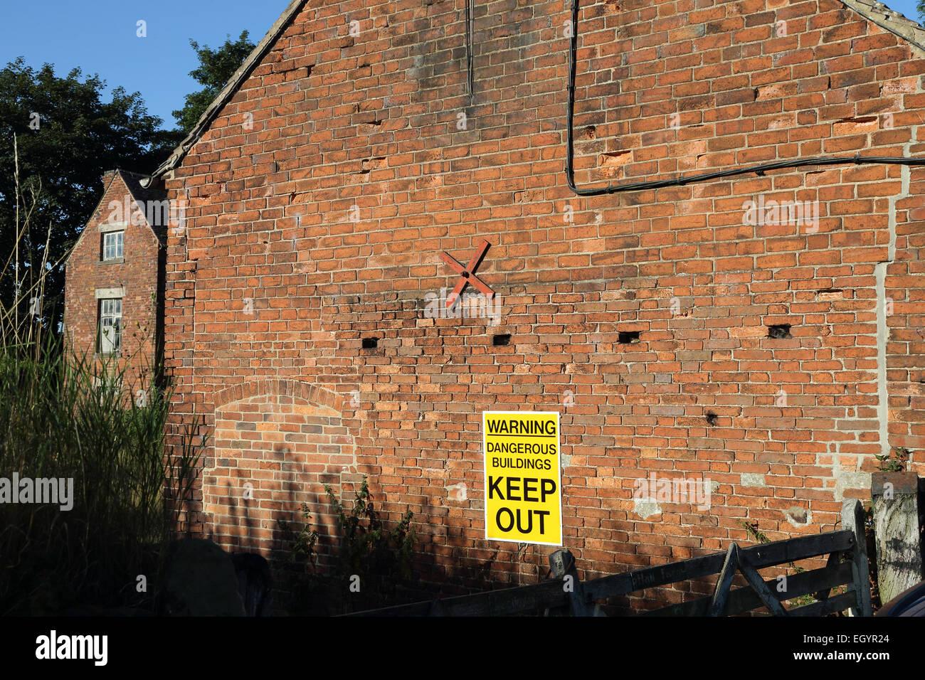 Avvertenza edifici pericolosi Tenere fuori segno sulla costruzione Immagini Stock