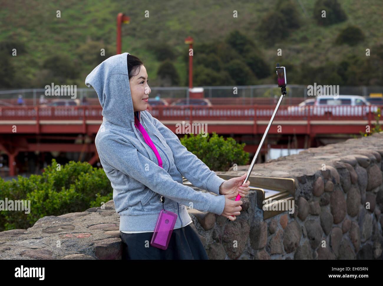 Donna asiatica, selfie stick, tenendo selfie, selfie foto, punto di vista, lato nord del Golden Gate Bridge, città Immagini Stock
