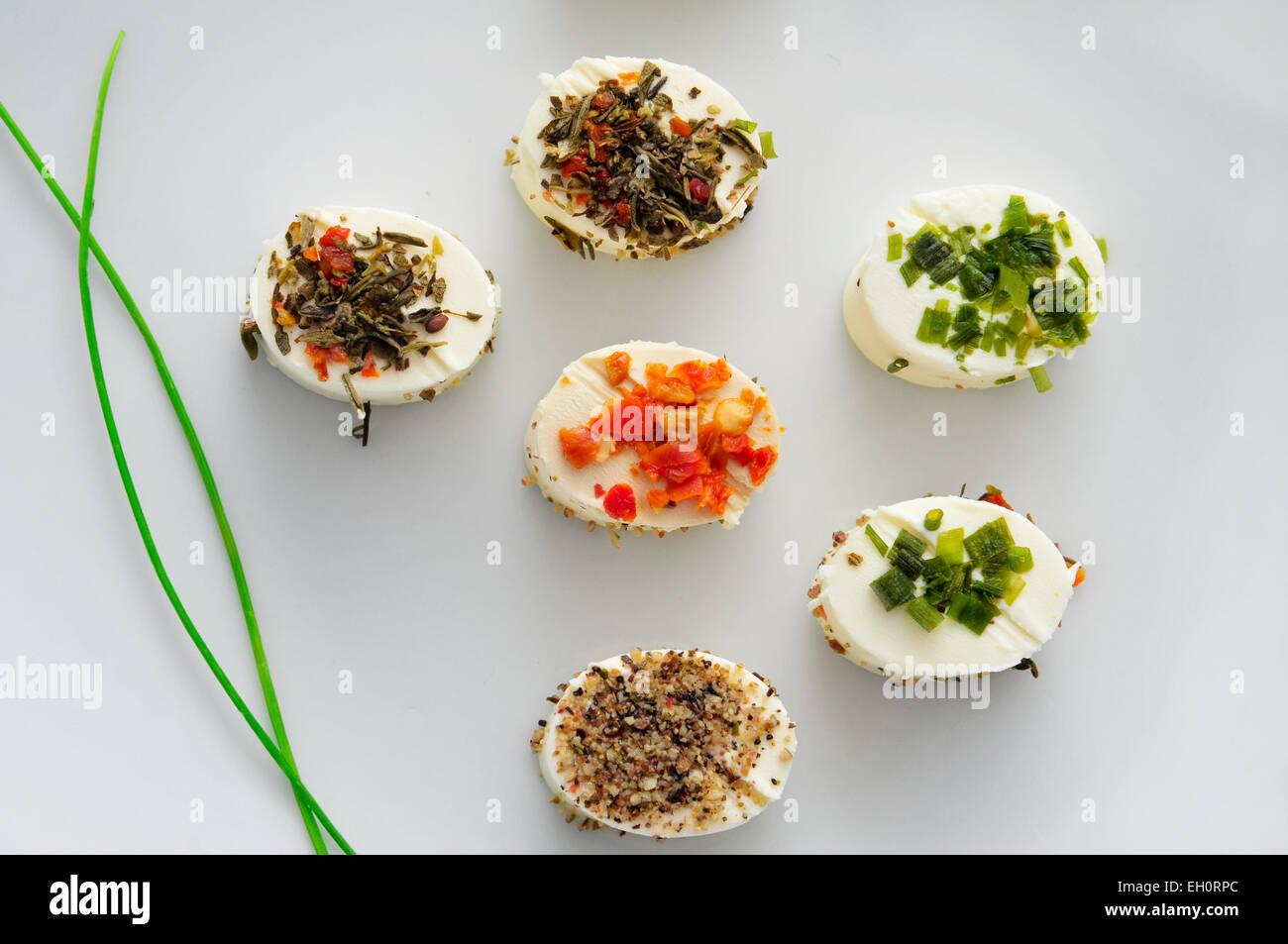 Una piastra con alcune diverse tartine, con crema di formaggio e spezie varie, servita come antipasto Immagini Stock