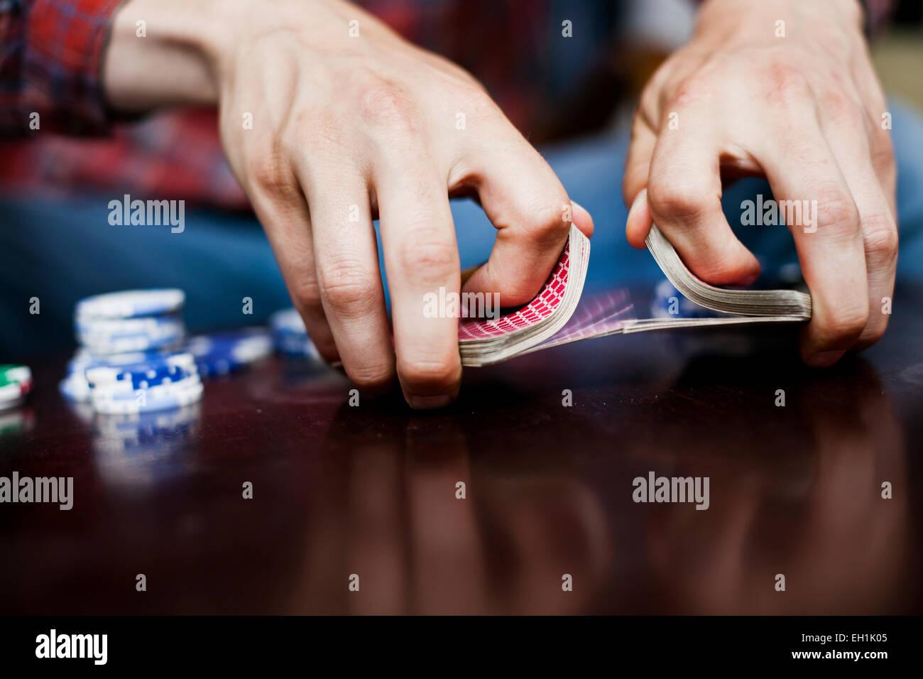 Immagine ritagliata delle mani dell'uomo e di miscelazione shuffling mazzo di carte Foto Stock