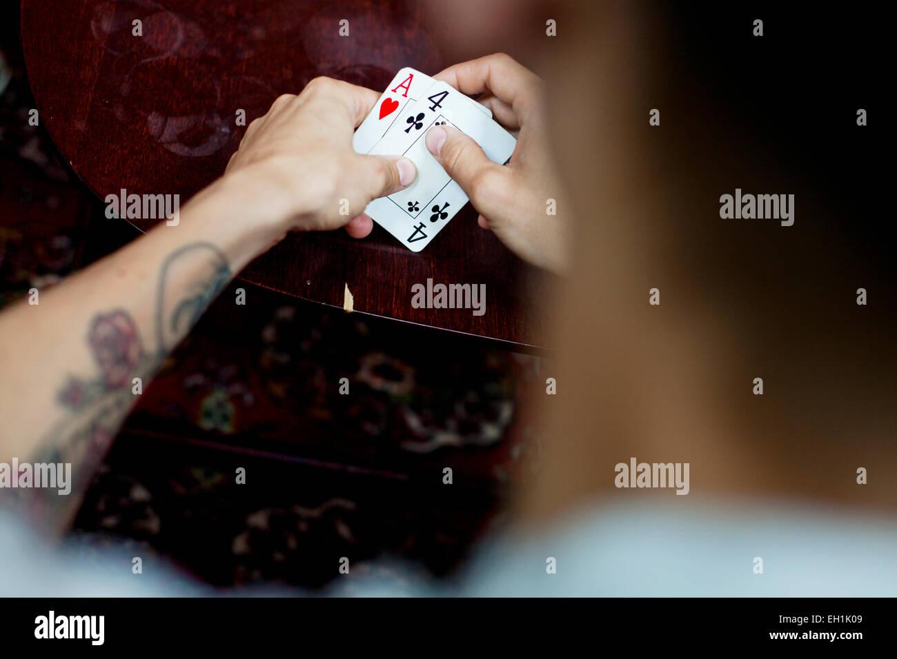 Immagine ritagliata dell'uomo giocando a carte a casa Immagini Stock