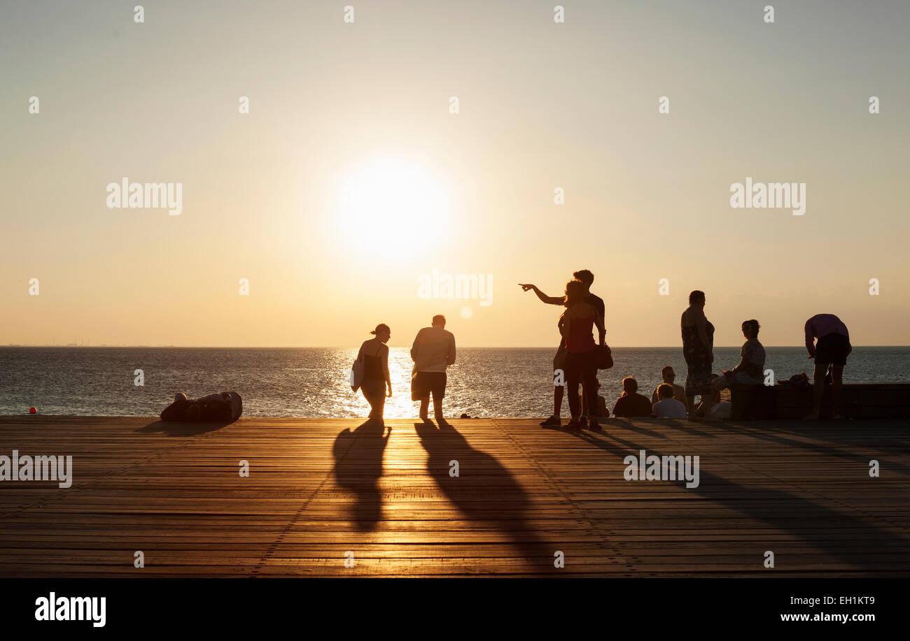 La gente sulla pedana contro il mare durante il tramonto Immagini Stock