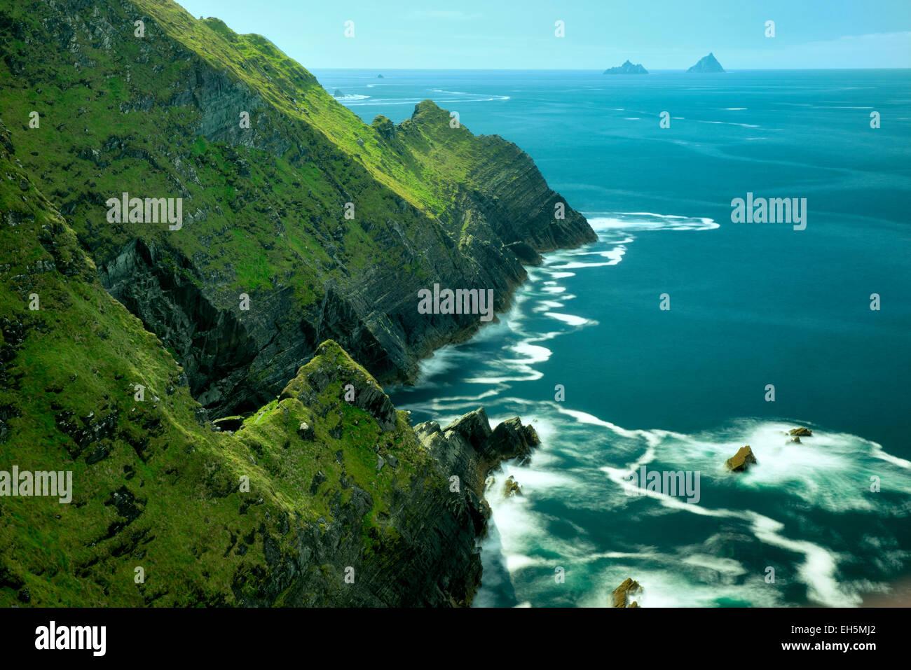 Kerry scogliere con schiuma d'onda sull'acqua. Portmagee, Ring of Kerry, Irlanda. Skellig Rocks in distanza Immagini Stock