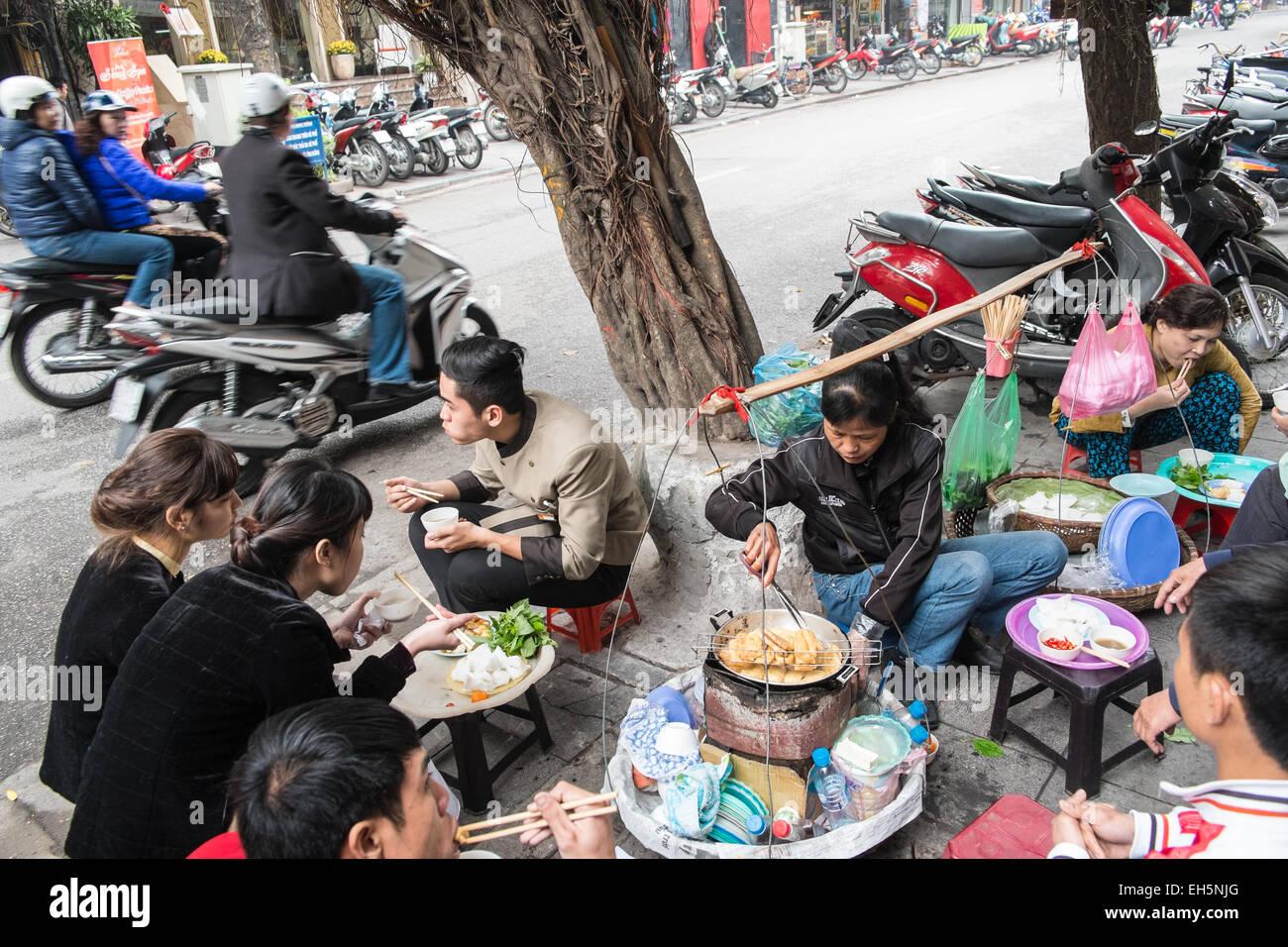 Seduti su sgabelli in plastica per una cucina di strada pasto