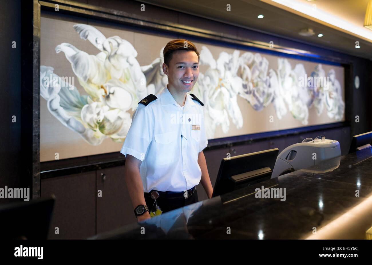 Un membro dell' equipaggio presso il banco informazioni a bordo di P & O Cruises nave più recente, Immagini Stock