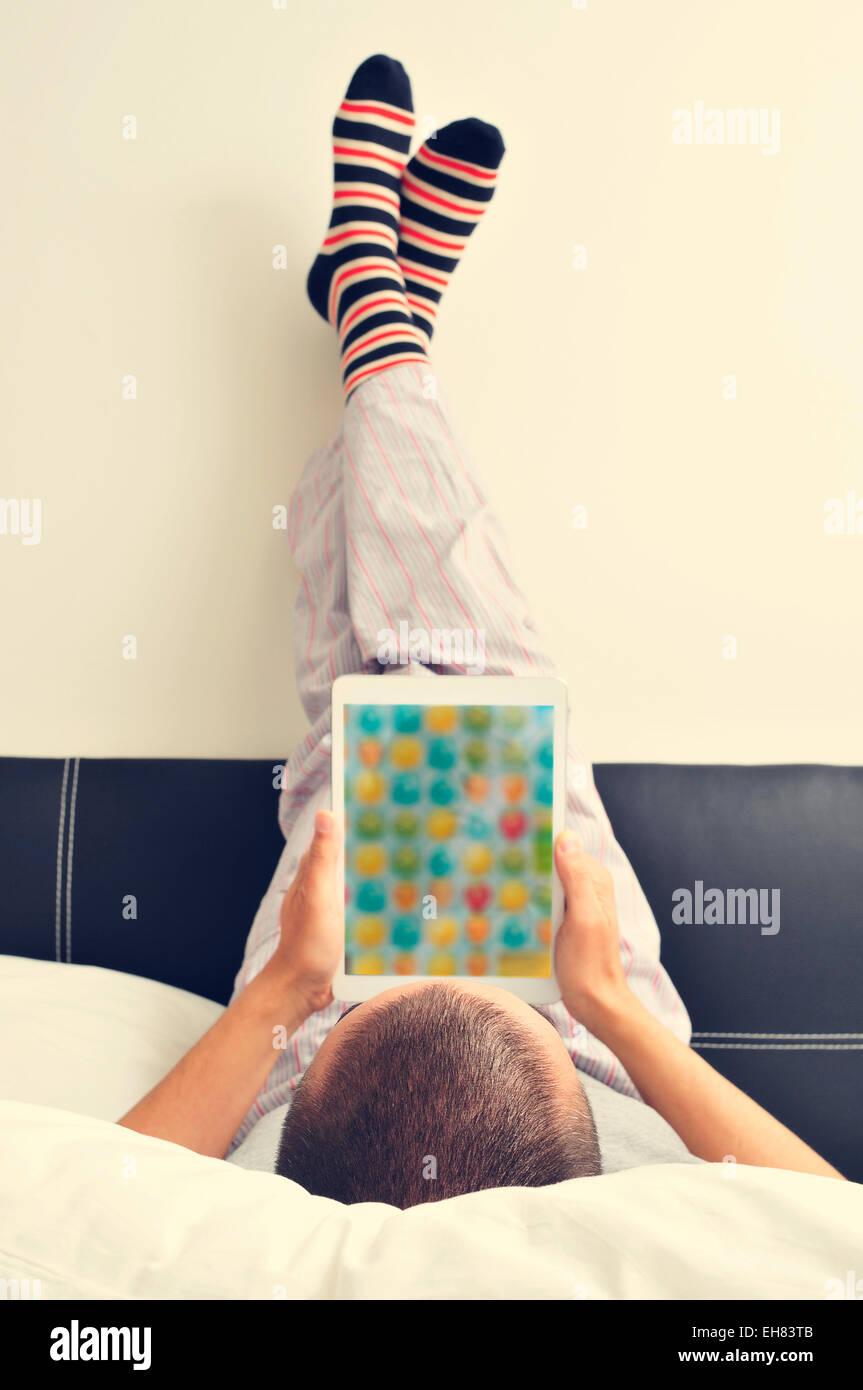 Un giovane uomo in pigiama nel letto di un tablet con i suoi piedi contro la parete Immagini Stock