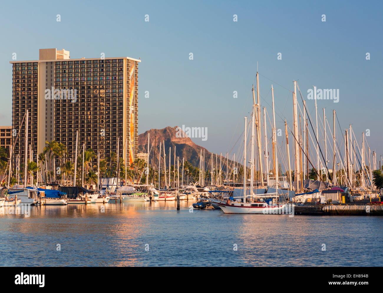 Waikiki Hawaii, con barche a vela in Ala Moana Harbour e l'Hilton Hawaiian Village resort dietro Immagini Stock
