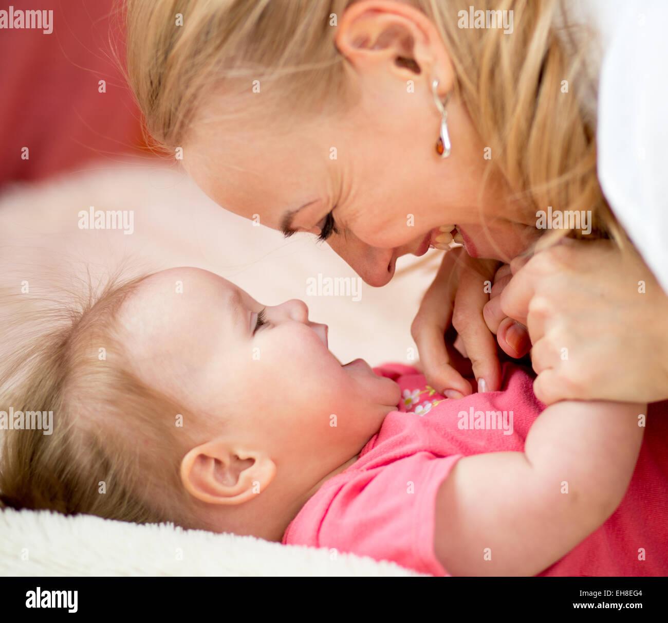 Mom guarda con amore al bambino. La genitorialità felicità concepimento. Immagini Stock