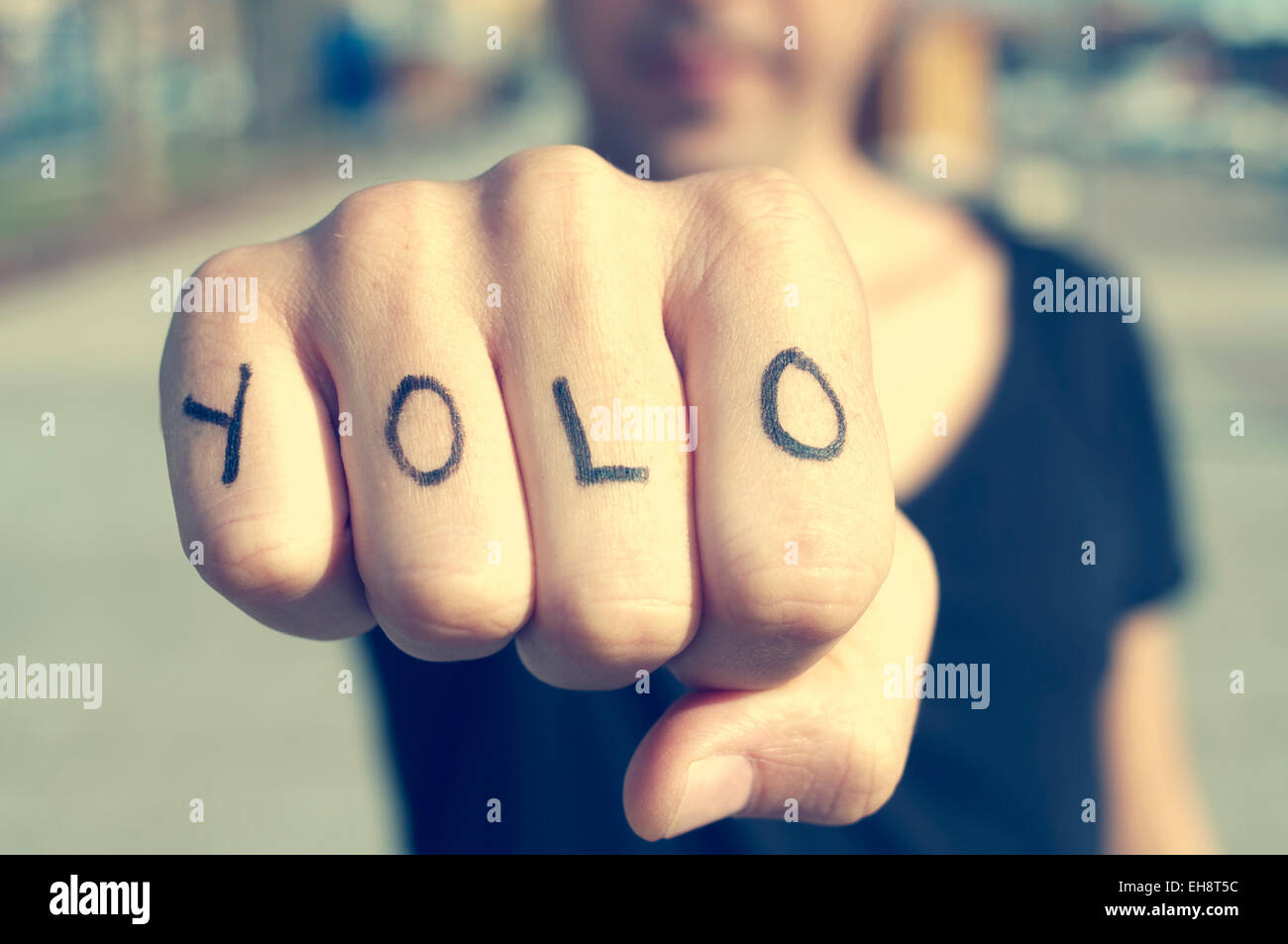 Primo piano di un giovane uomo con la parola yolo, per si vive una volta sola, tatuato sulla sua mano, con un effetto Immagini Stock