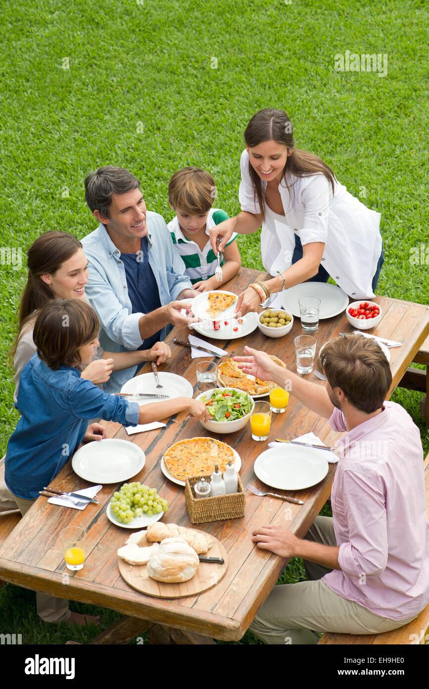 La famiglia e gli amici con picnic mentre è in vacanza Immagini Stock
