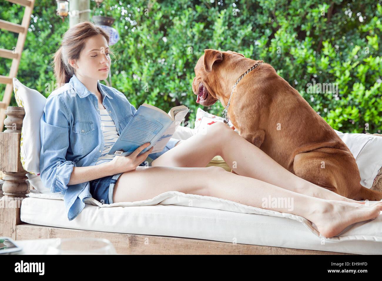 Giovane donna seduta accanto al cane all'aperto, libro di lettura Immagini Stock