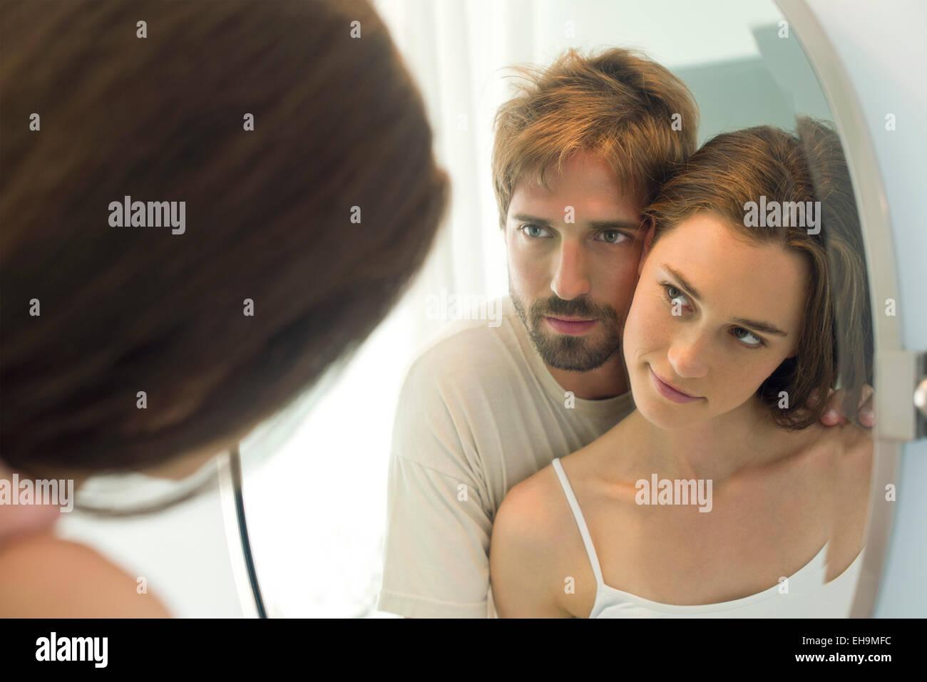 Giovane guancia a guancia, guardando ogni altro in specchio Immagini Stock