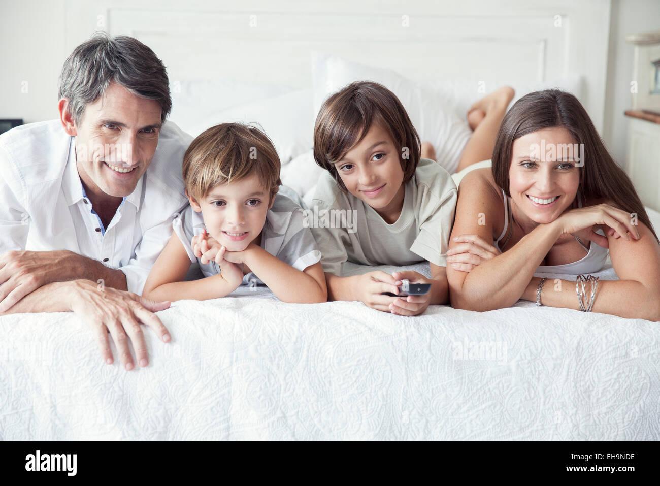 Famiglia di guardare la TV sul letto, ritratto Immagini Stock