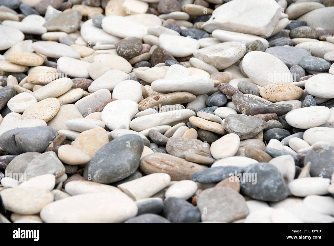 Ciotoli arrotondati in sfumature di grigio, blu, bianco panna e arancione diffondono la spiaggia di Bridlington, Immagini Stock
