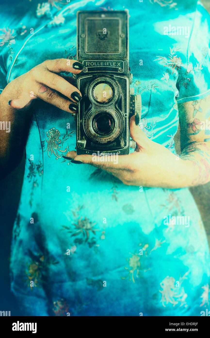 Donna che indossa un abito cinese tenendo un vintage fotocamera Rolleiflex Foto Stock