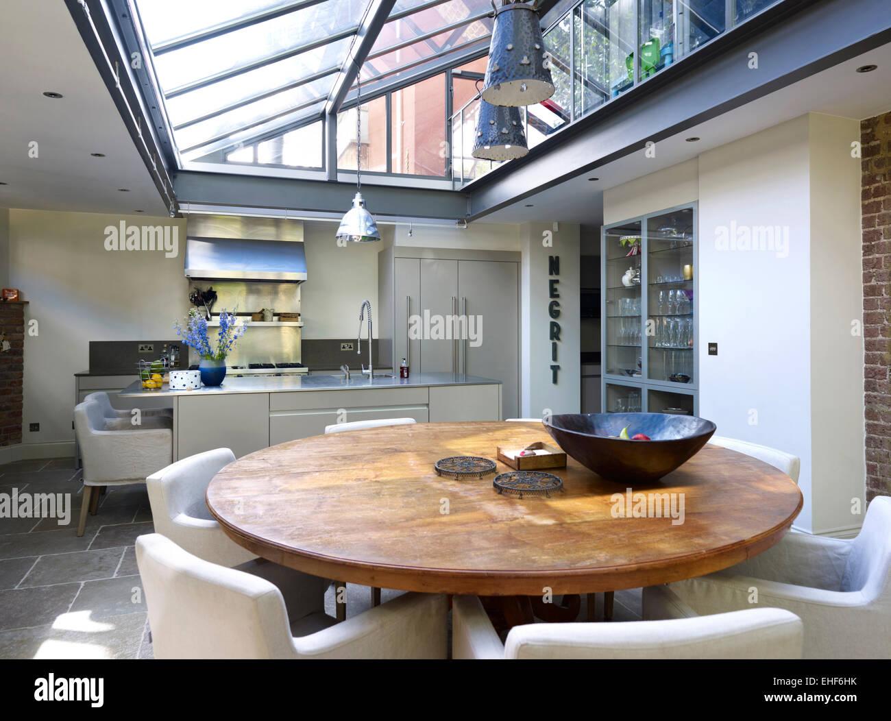 Round tavolo in legno con sedie in vetro con tetto di cucina e area ...