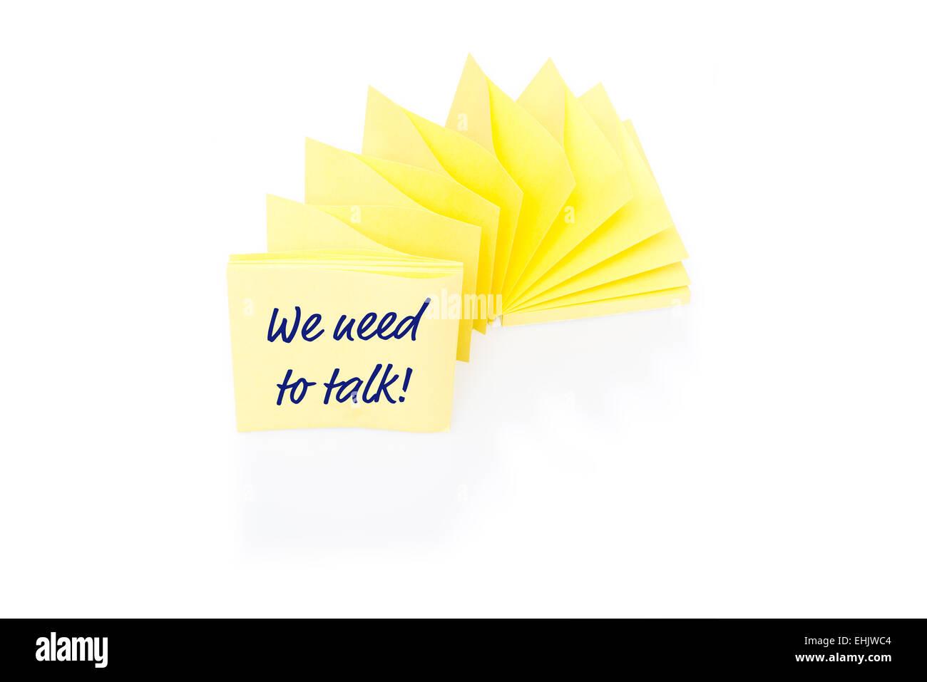 Bigliettino giallo sul blocco con il messaggio di cui abbiamo bisogno per parlare Immagini Stock