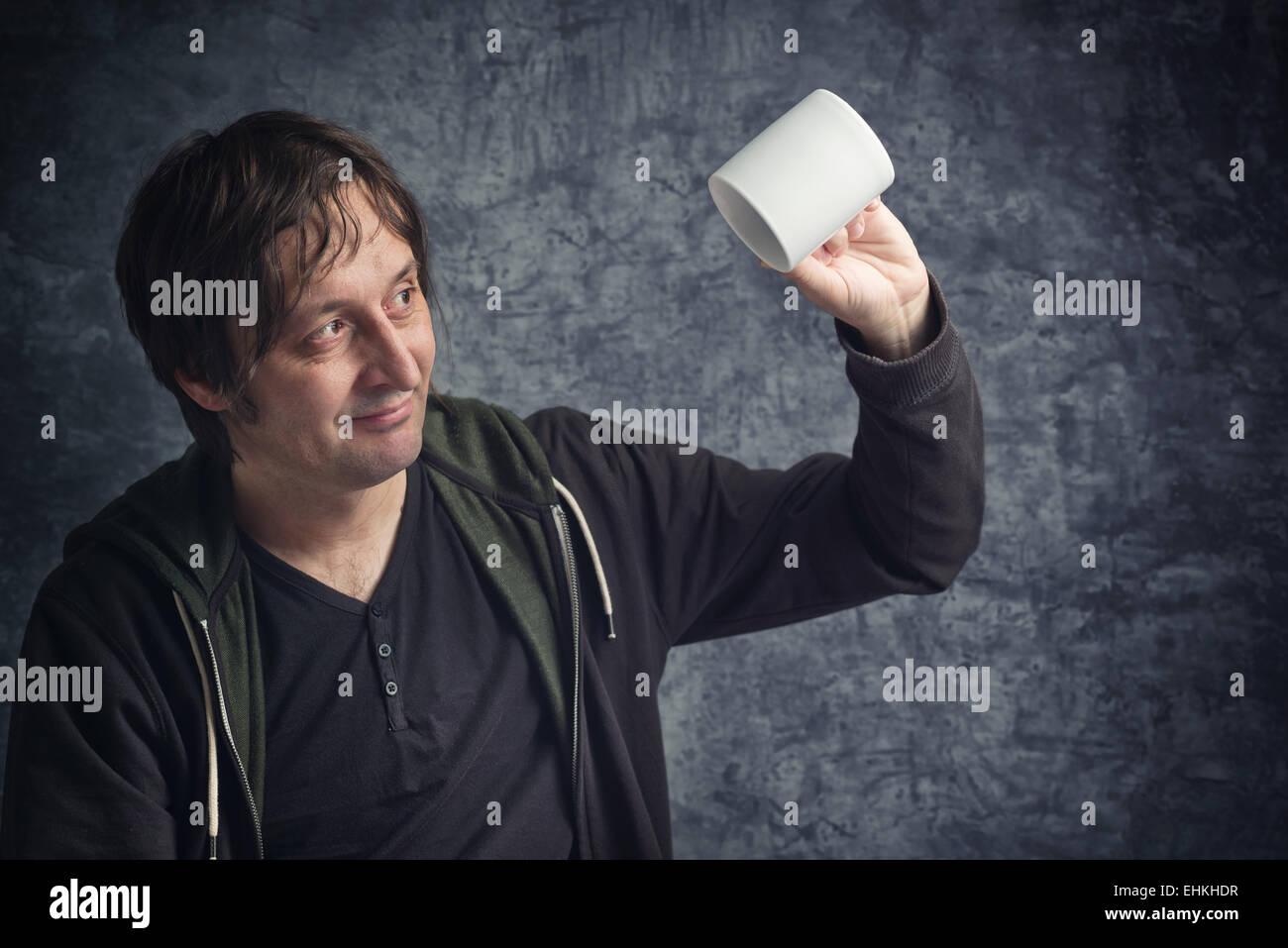Uomo deluso guardando a tazza vuota, il concetto di fallimento di aspettative. Immagini Stock