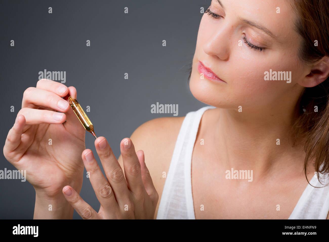 Donna che mantiene la fiala di vetro di vitamina D. Immagini Stock