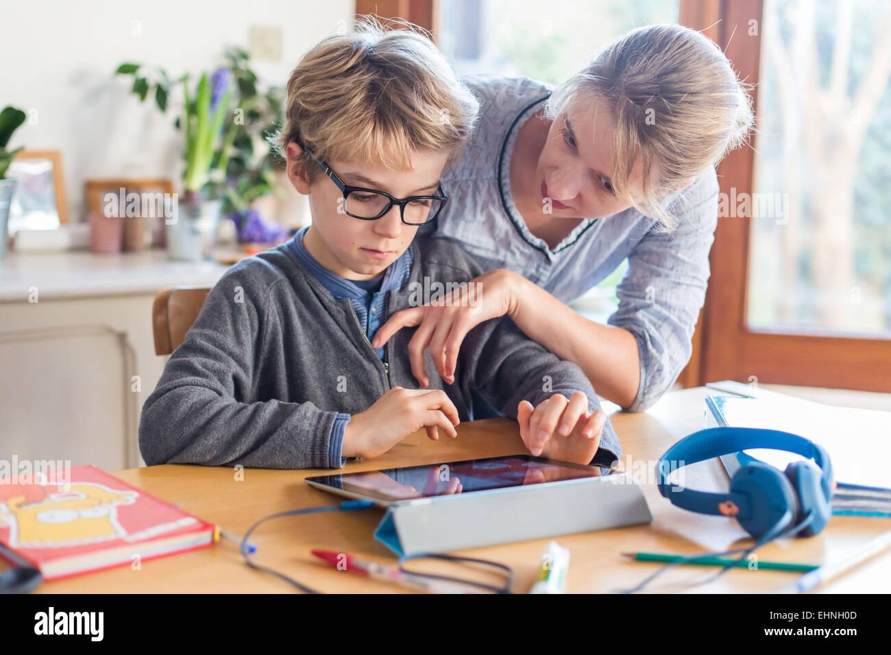 8 anno vecchio ragazzo utilizzando computer tablet. Immagini Stock