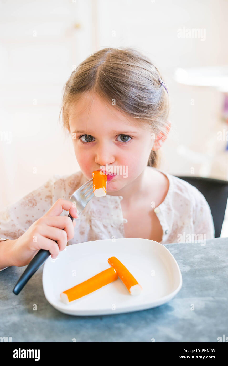 5 anno-vecchia ragazza mangiare surimi. Immagini Stock