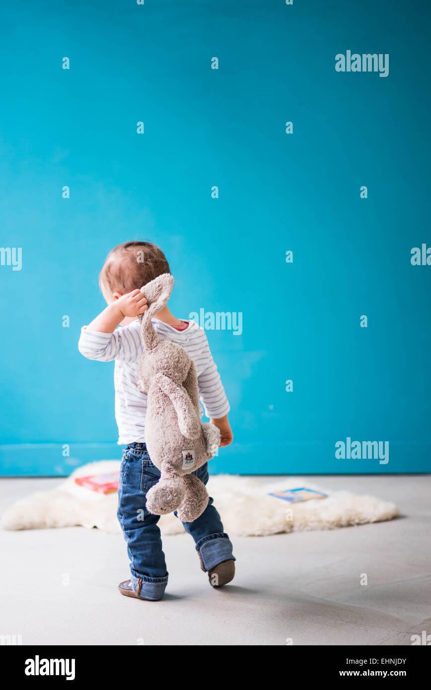 Bambino a piedi dalla fotocamera con il giocattolo di coniglio sulla spalla Immagini Stock