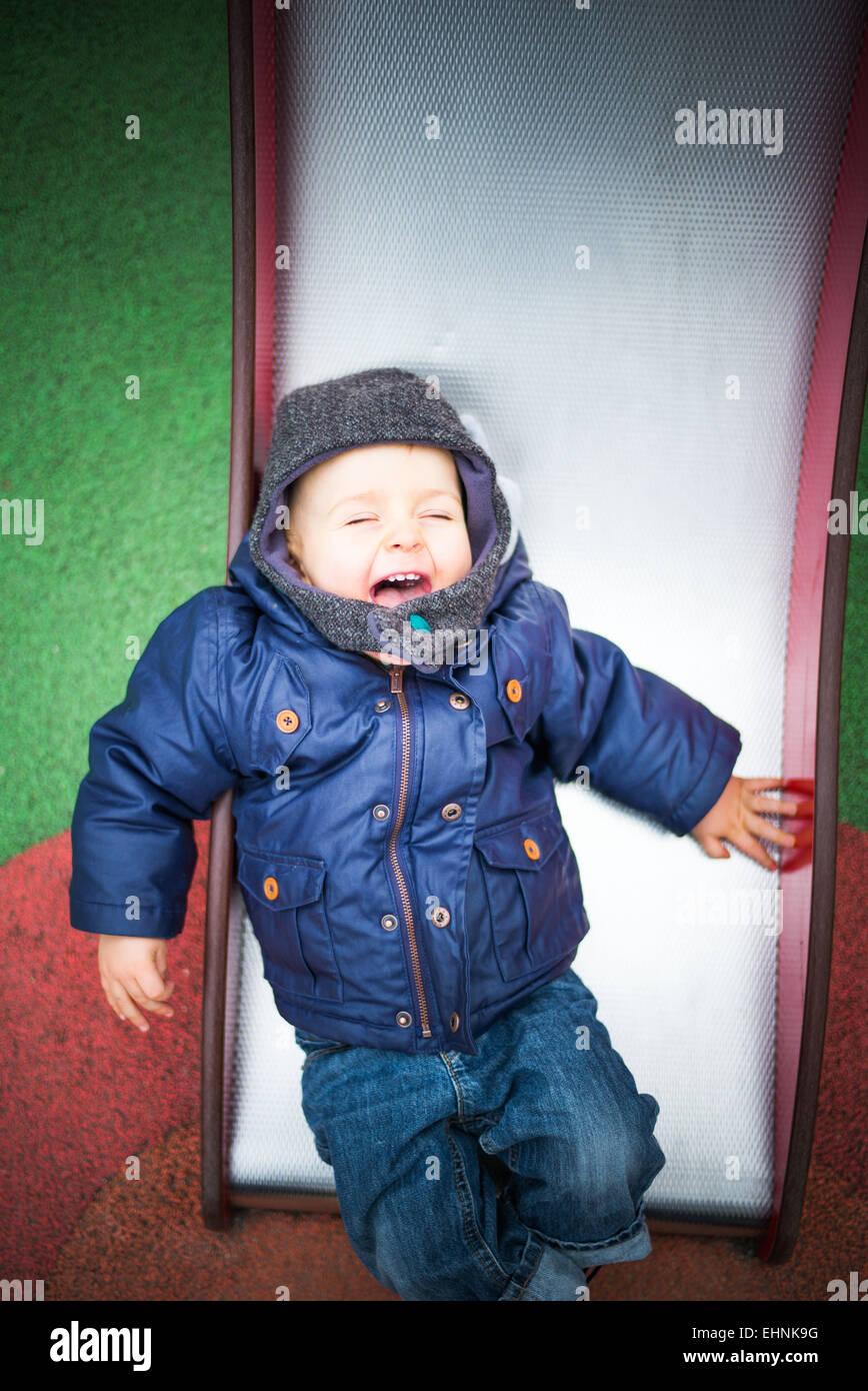 18 mese-vecchio baby boy su una diapositiva in un parco giochi. Immagini Stock
